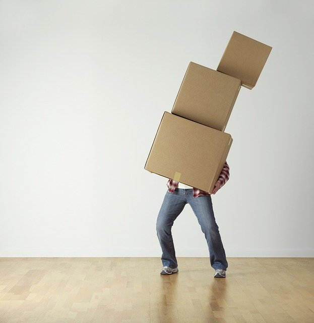 A man carrying a pile of cardboard boxes while preparing for intercity relocation.