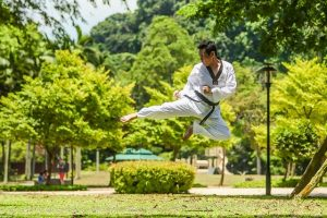 A man in the air during his martial arts workout.