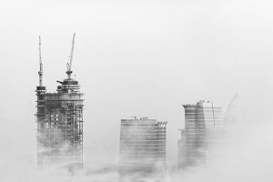 Dubai skyscrapers under construction surrounded by fog.
