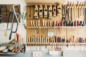 Tools in a garage as an example of hoe to organize your garage space to add more room.