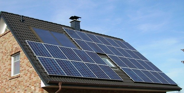A house with solar panels on the roof, an example of zero energy homes.