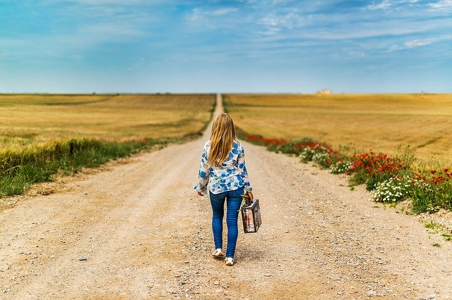A woman with a suitcase on a dirt road
