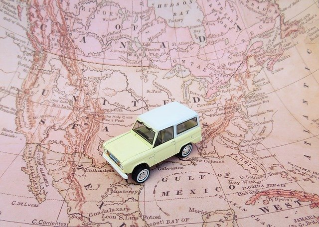 A car toy on a map, symbolizing a road trip, one of the reasons why owning a car in 2020 is a good idea.
